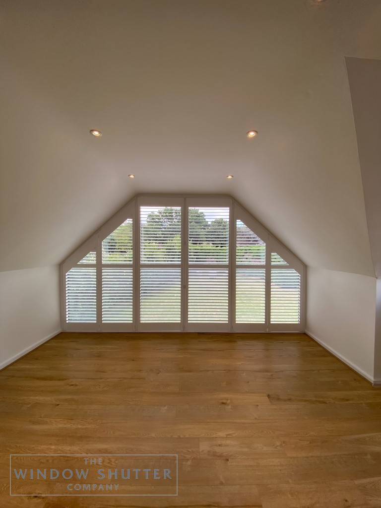 Shaped shutter solution for raked windows in High Wycombe, full room, louvres open